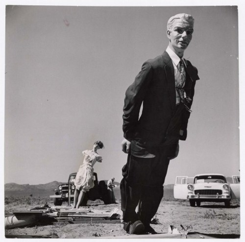 mpdrolet:      Scorched and disheveled male mannequin clad in dark business suit standing in desert with lady mannequin in background, 7,000 ft. from the 44th nuclear test explosion, a day after the blast, indicating that humans could be burnt but still alive, 1955      Loomis Dean