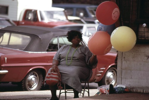 Woman selling Have A Nice Day balloons on a Chicago South Side street corner at Sox Park Baseball Field, June 1973.